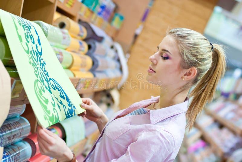 Mujer con los rollos del papel pintado imagenes de archivo