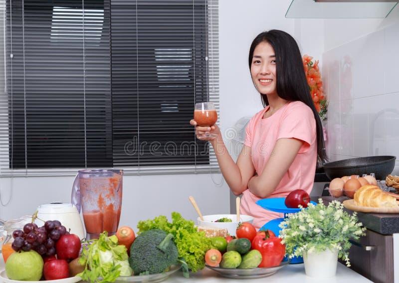 Mujer con los smoothies en vidrio en el sitio de la cocina foto de archivo