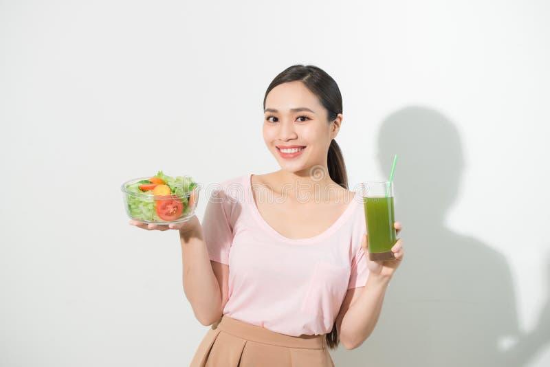 Mujer con los smoothies verdes del detox, ensalada en el bol de vidrio aislado en el fondo blanco Nutrici?n apropiada, comida veg imagenes de archivo
