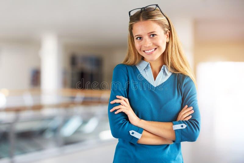 Mujer con los vidrios en centro de negocios con las manos cruzadas fotos de archivo