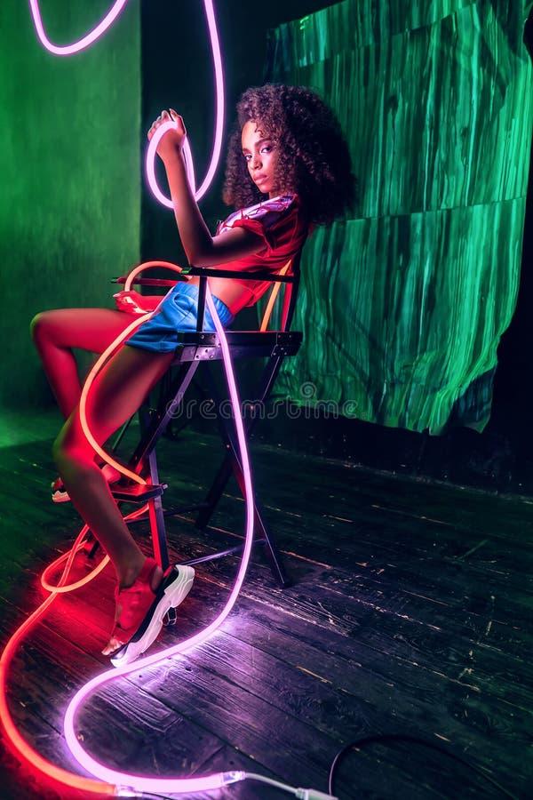 Mujer con luz de neón rosa y rojo alrededor del cuerpo y la silla foto de archivo