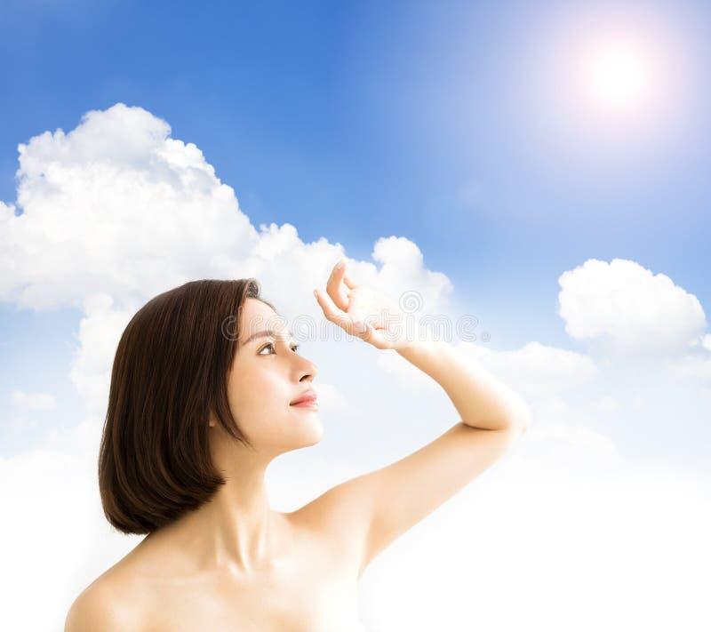 Mujer con luz del sol cuidado de piel y concepto ULTRAVIOLETA del bloque del sol fotos de archivo