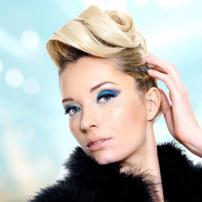 Mujer con maquillaje del peinado de la moda y del ojo azul fotografía de archivo