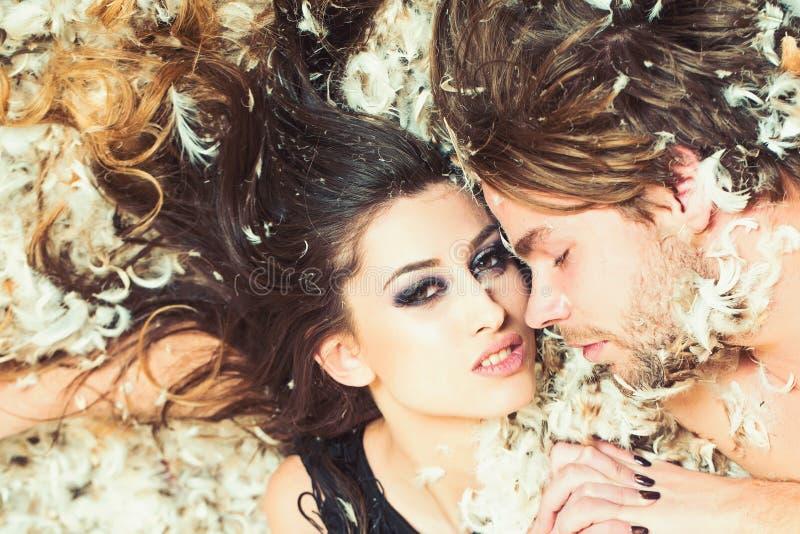 Mujer con maquillaje y machista durmiente, relaciones La mujer y el hombre sensuales se relajan en la pluma, amor Júntese en amor imagen de archivo libre de regalías