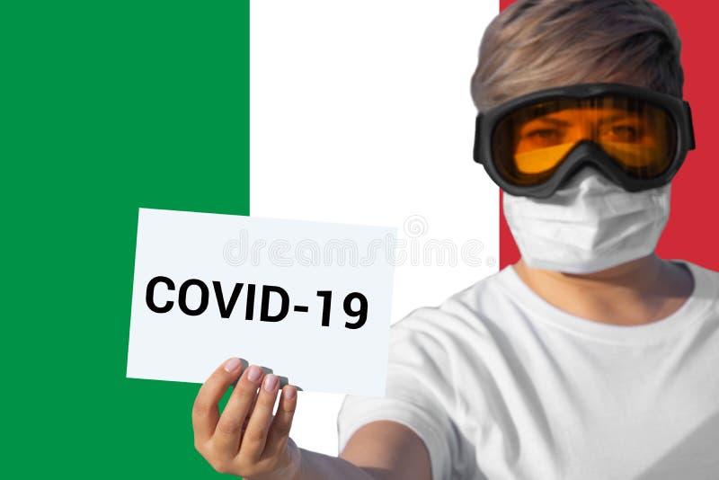 Mujer con mascarilla en la hoja con inscripción COVID-19 contra bandera italiana imagen de archivo