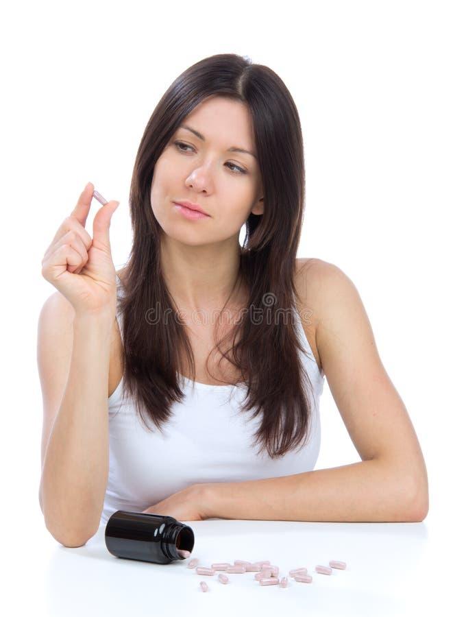 Mujer con mirada del dolor de cabeza en las tablillas de la medicina de las píldoras foto de archivo