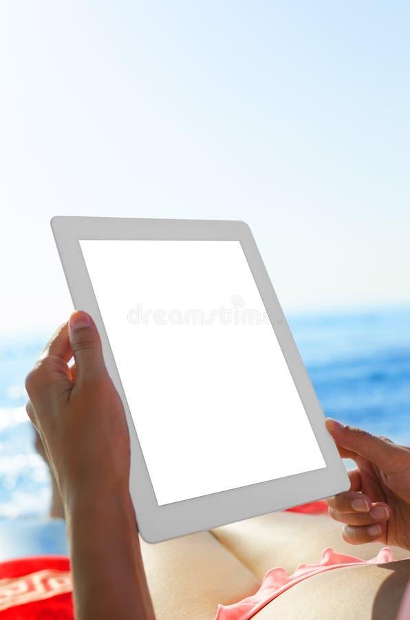 Mujer con PC de la tableta en la playa fotos de archivo