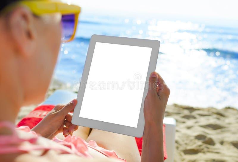 Mujer con PC de la tableta en la playa imagen de archivo libre de regalías