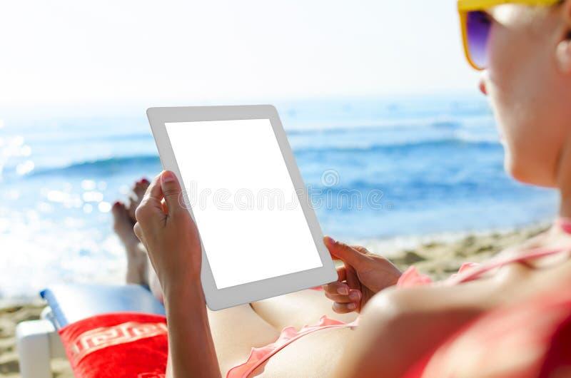 Mujer con PC de la tableta en la playa fotos de archivo libres de regalías