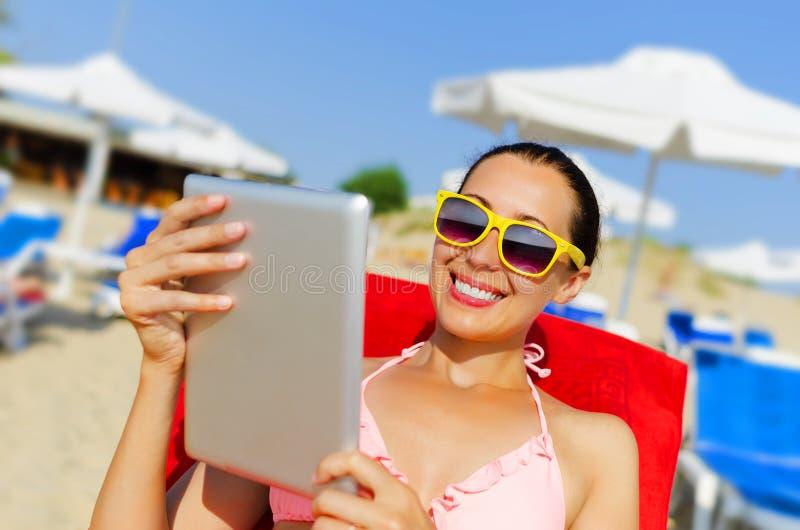 Mujer con PC de la tableta en la playa fotografía de archivo libre de regalías