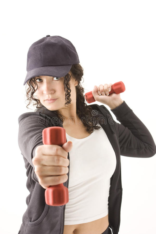 Mujer con pesas de gimnasia rojas en manos imagen de archivo