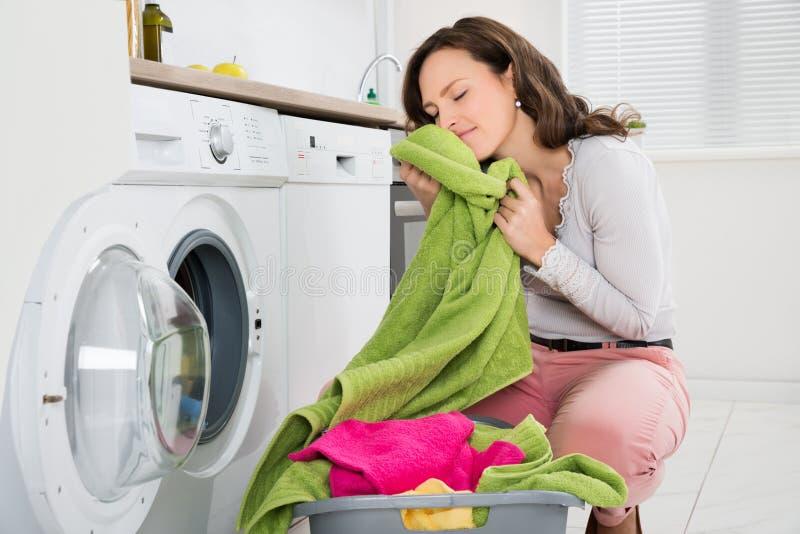 Mujer con ropa cerca de la lavadora imagenes de archivo