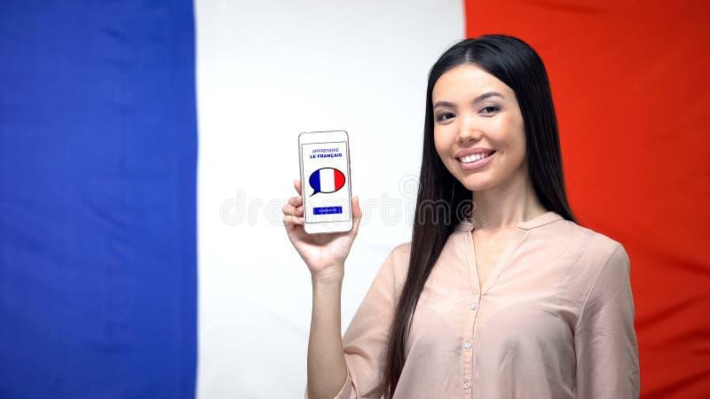Mujer con smartphone contra el fondo francés de la bandera, app del estudio de la lengua imagen de archivo