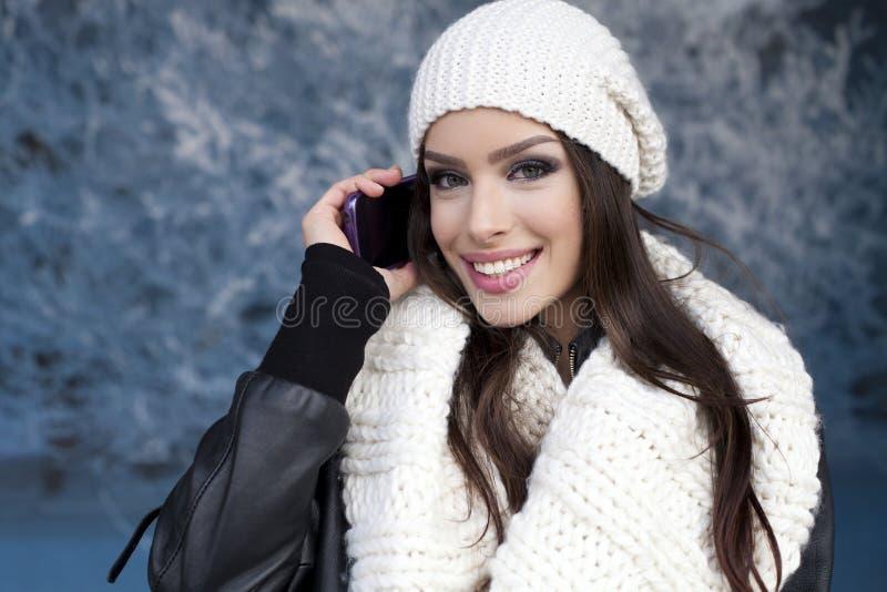 Mujer con sonrisa usando un teléfono elegante imagen de archivo libre de regalías