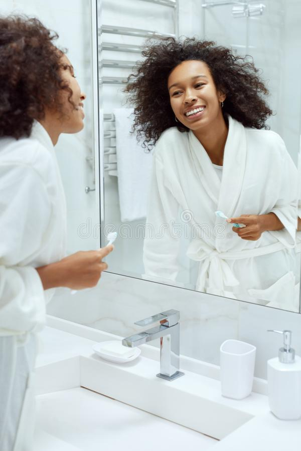 Mujer con sonrisa y belleza mirando el espejo en el baño fotografía de archivo