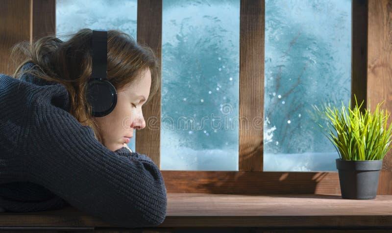 Mujer con suéter de lana escuchando música en el suelo con una ventana acogedora de nieve en invierno fotografía de archivo libre de regalías