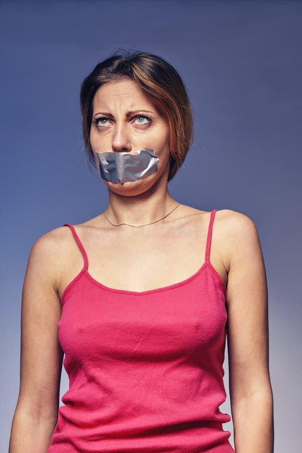 Mujer con su boca pegada con la cinta Concepto en la humillación y la discriminación de mujeres foto de archivo libre de regalías
