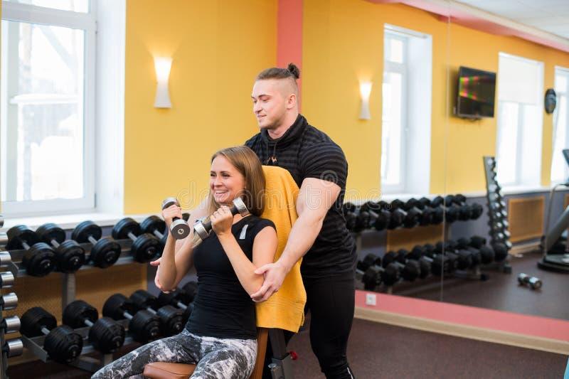 Mujer con su instructor personal de la aptitud en el gimnasio que ejercita la gimnasia del poder con un barbell imágenes de archivo libres de regalías
