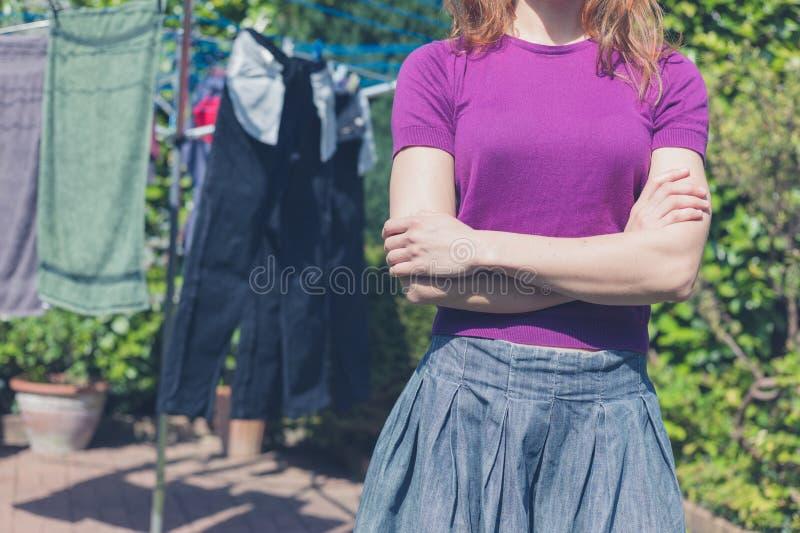 Mujer con su lavadero afuera en jardín imagen de archivo