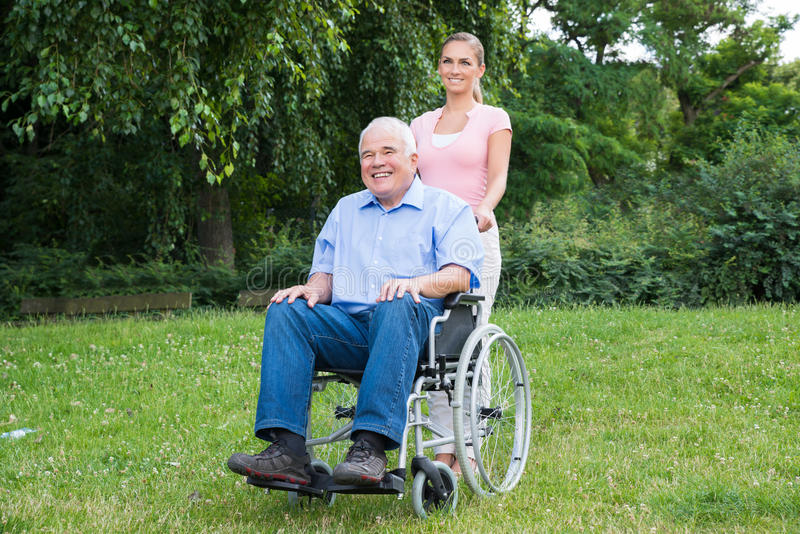 Mujer con su padre discapacitado On Wheelchair fotografía de archivo libre de regalías