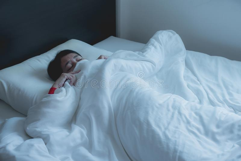 Mujer con susto y pánico mientras que se acuesta debajo de la manta en dormitorio, pesadilla o mún sueño foto de archivo