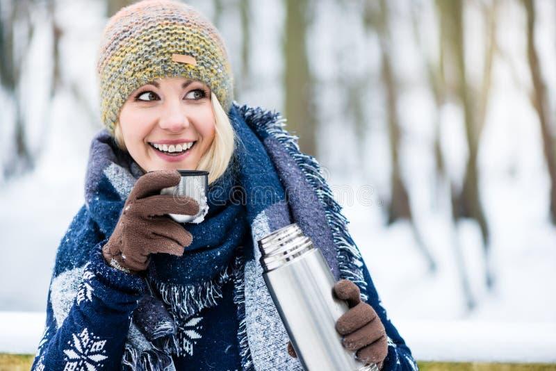 Mujer con té o café caliente en un alza del invierno fotos de archivo