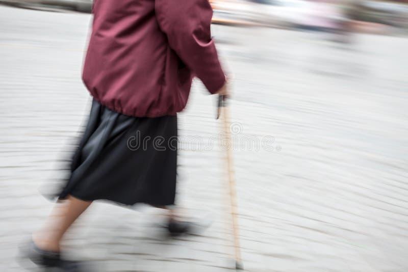 Mujer con un bastón que camina abajo de la calle imagen de archivo libre de regalías