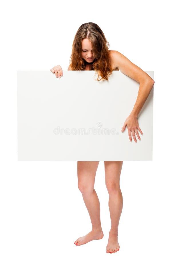 Mujer con un cartel que cubre su desnudez en un blanco fotografía de archivo