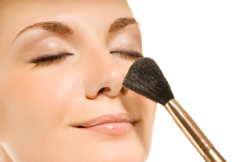 Mujer con un cepillo del maquillaje fotos de archivo