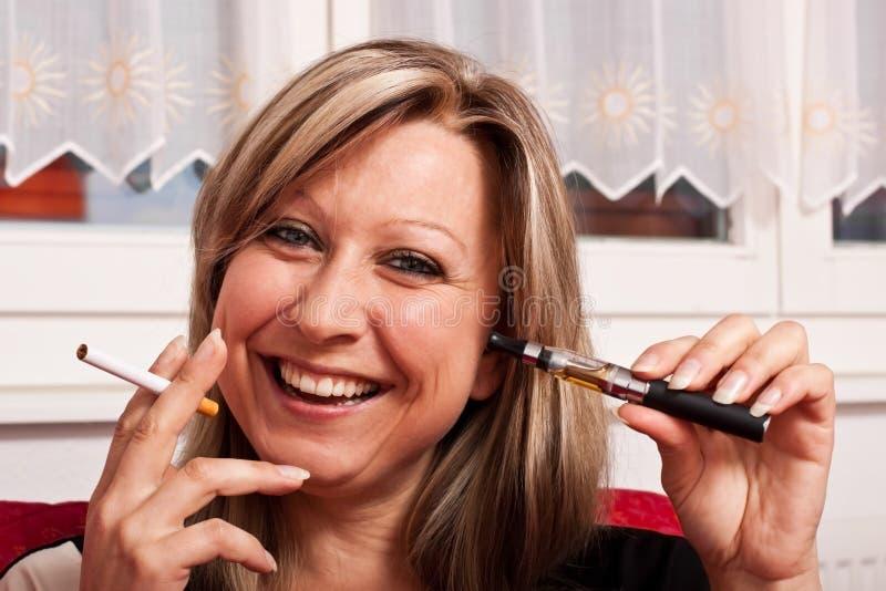 Mujer con un cigarrillo normal y eléctrico jovenes foto de archivo