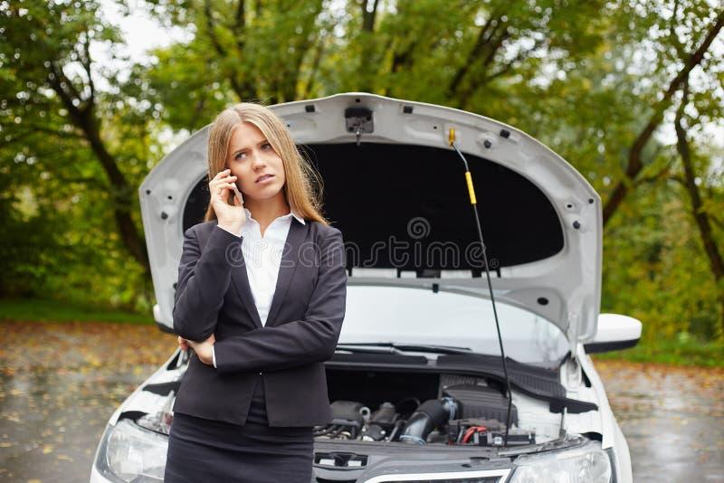Mujer con un coche quebrado fotos de archivo