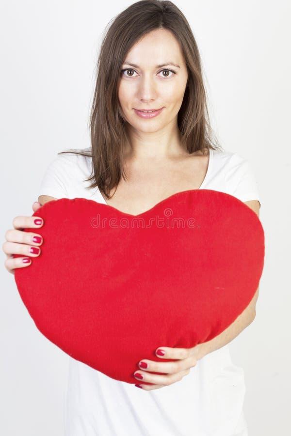 Mujer con un corazón rojo grande imagenes de archivo