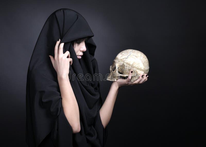 Mujer con un cráneo humano en negro imagen de archivo libre de regalías