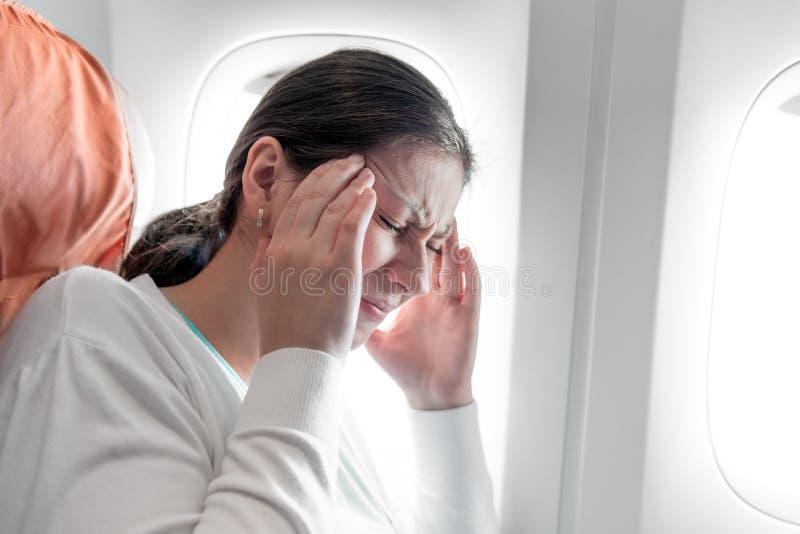 Mujer con un dolor de cabeza en un aeroplano fotos de archivo