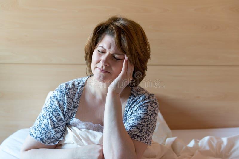 Mujer con un dolor de cabeza que se sienta en cama fotos de archivo libres de regalías