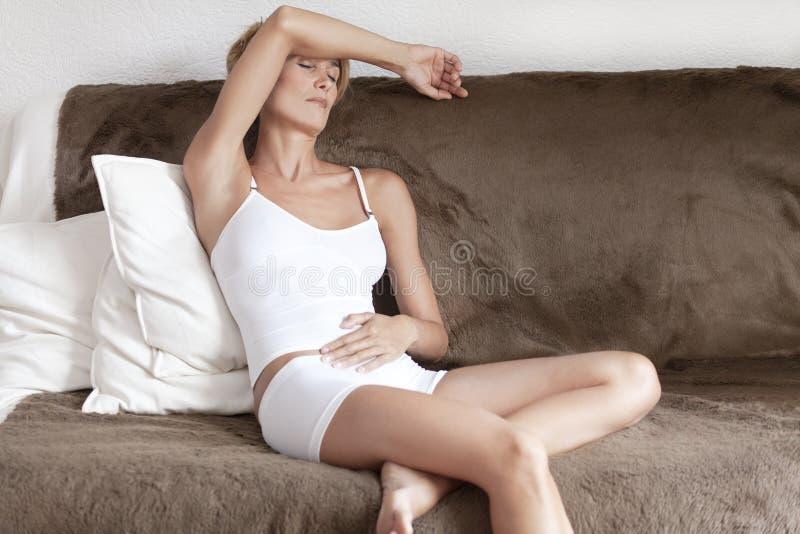 Mujer con un dolor de estómago fotografía de archivo