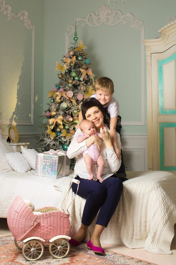 Mujer con un niño recién nacido en el cuarto de la Navidad un cochecito de niño imagen de archivo