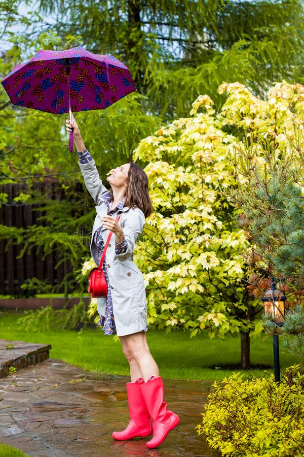 Mujer con un paraguas, botas de goma rojas que llevan y un impermeable bajo la lluvia en un jardín floreciente de la primavera imagenes de archivo