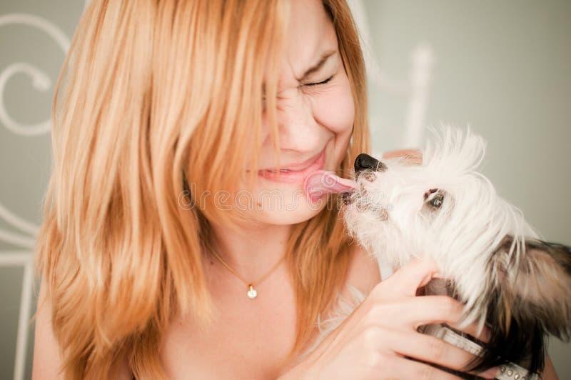 Mujer con un pequeño perro lindo imagenes de archivo