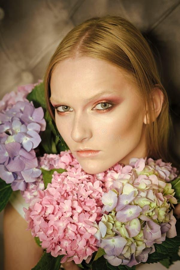 Mujer con un ramo de hortensias Mujer joven de la belleza, pelo rubio con la hortensia imagenes de archivo