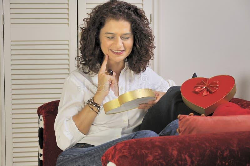 Mujer con un rectángulo de chocolates imagenes de archivo