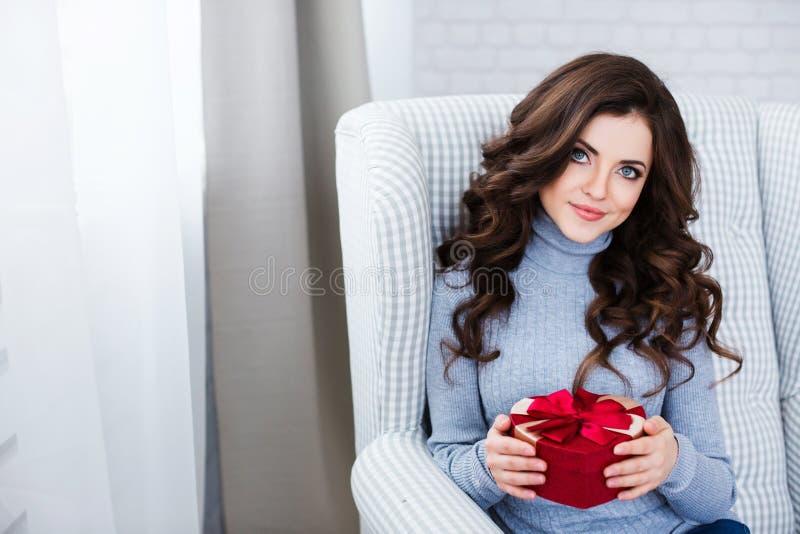 Mujer con un regalo en la forma de un corazón en una silla cómoda en casa fotos de archivo