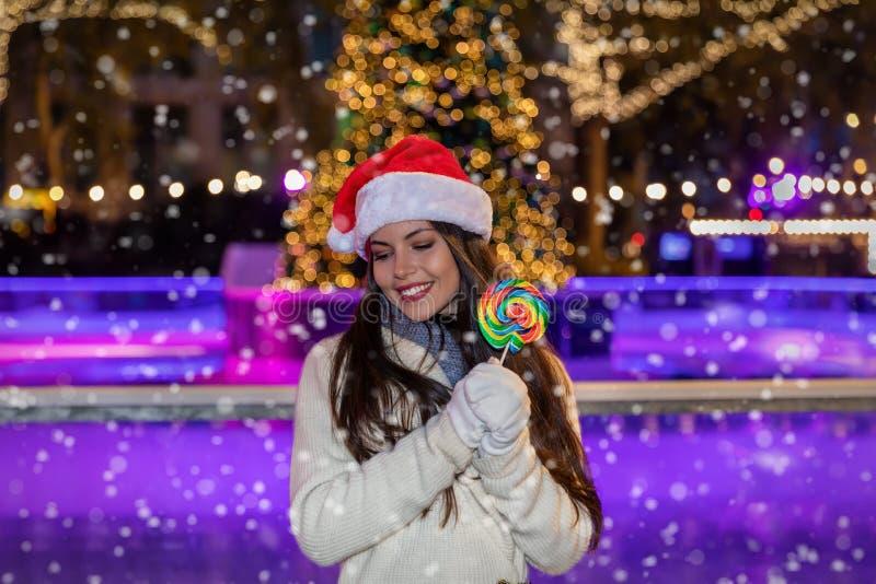 Mujer con un sombrero de Papá Noel delante de una pista de hielo de la Navidad fotos de archivo