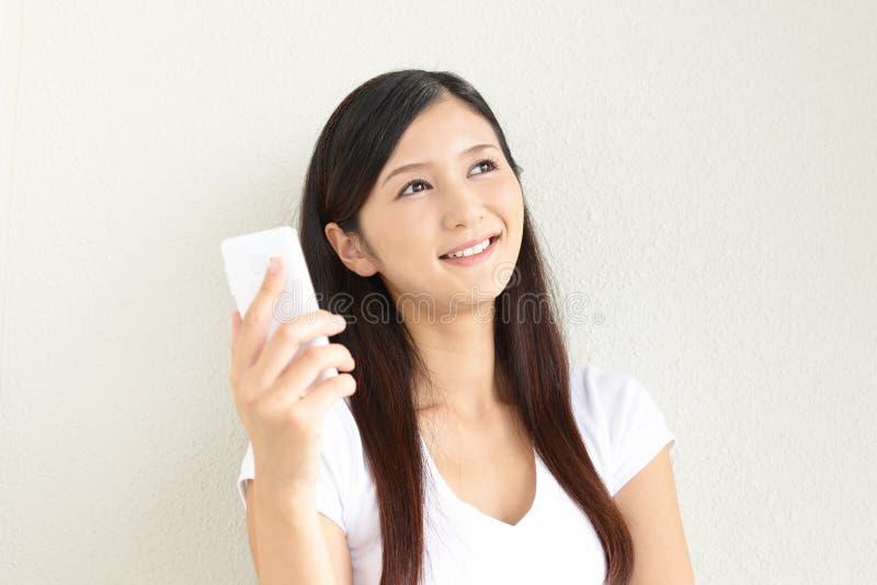 Mujer con un teléfono elegante imagenes de archivo