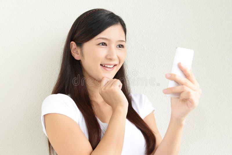 Mujer con un teléfono elegante imagen de archivo