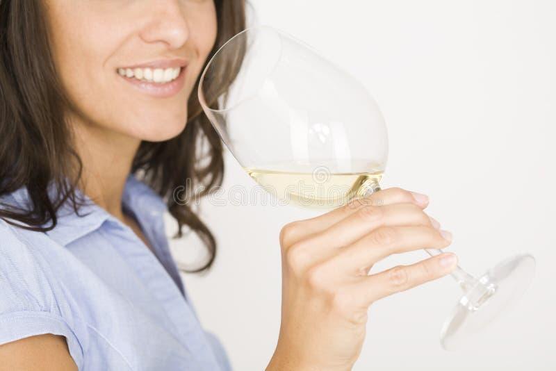 Mujer con un vidrio de vino blanco imagen de archivo
