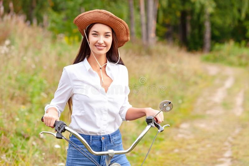 Mujer con una bicicleta negra en un parque del verano fotografía de archivo libre de regalías