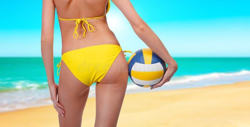Mujer con una bola en una playa imagenes de archivo