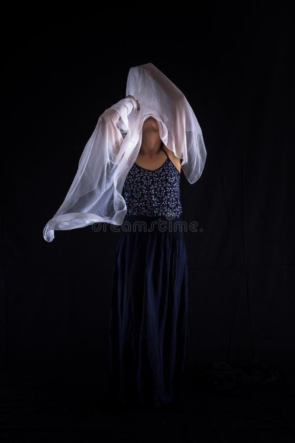 Mujer con una bufanda blanca en un fondo negro foto de archivo libre de regalías