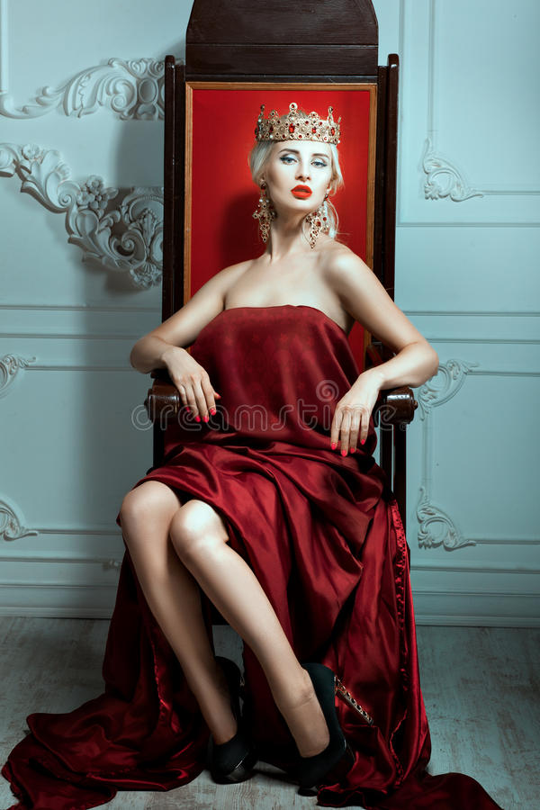 Mujer con una corona su cabeza que se sienta en el trono foto de archivo